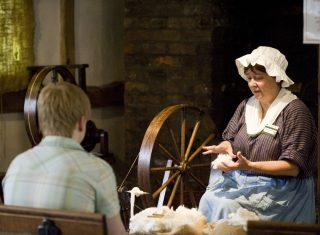 The National Trust Hand Spinning & Weaving Co-ordinator, dressed in costume, shows visitors how the cotton was processed at Quarry Bank Mill, Styal, Cheshire.